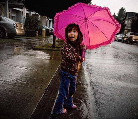 Ecstatic to use her new umbrella and boots to splash in the rain.